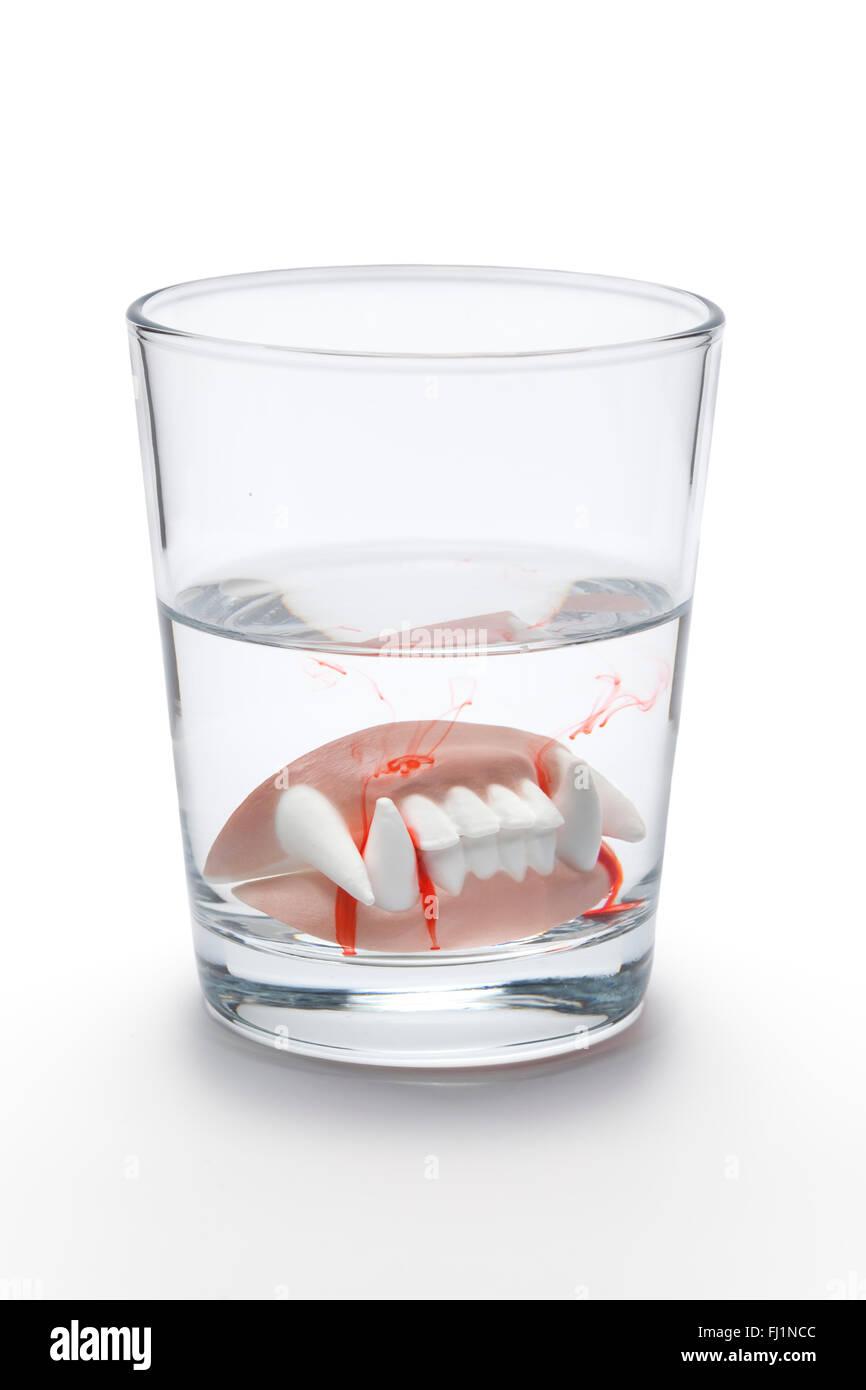 Protesi dentale con il sangue di un vampiro in un bicchiere di acqua su sfondo bianco Immagini Stock
