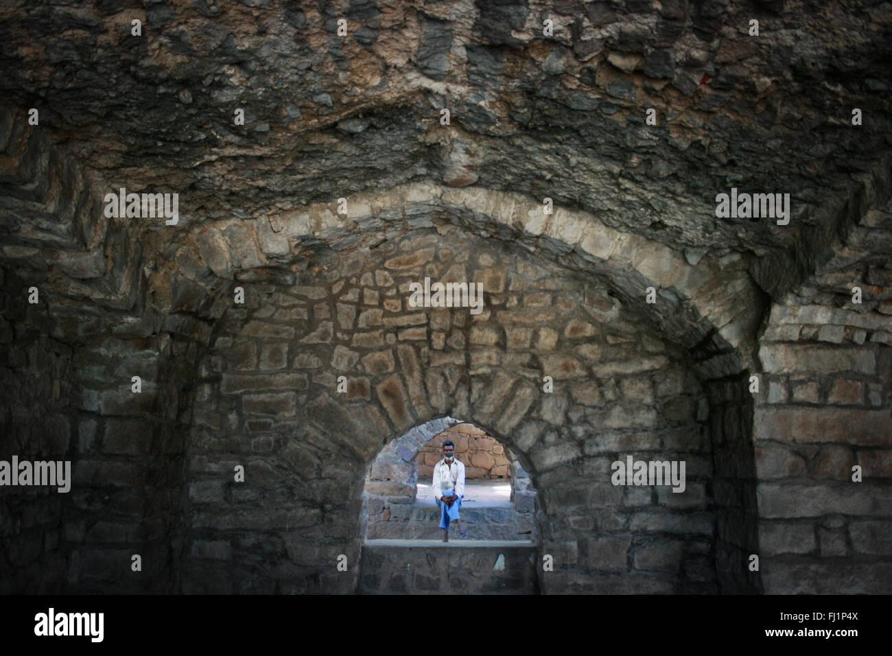 Uomo seduto all'interno di fort di Hyderabad, India Immagini Stock