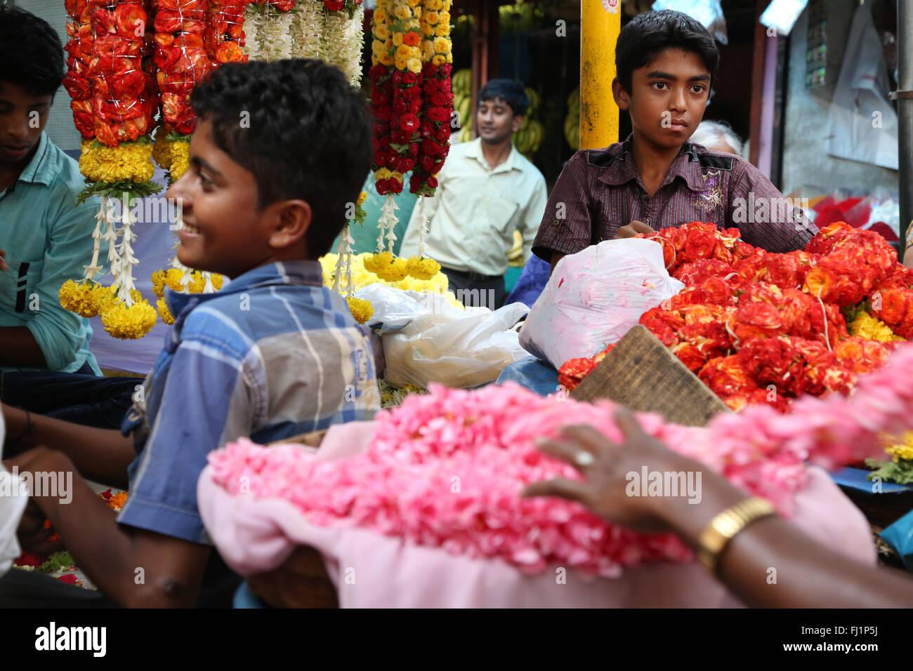 Giovani ragazzi che vendono fiori al mercato Devaraja, Mysore Immagini Stock