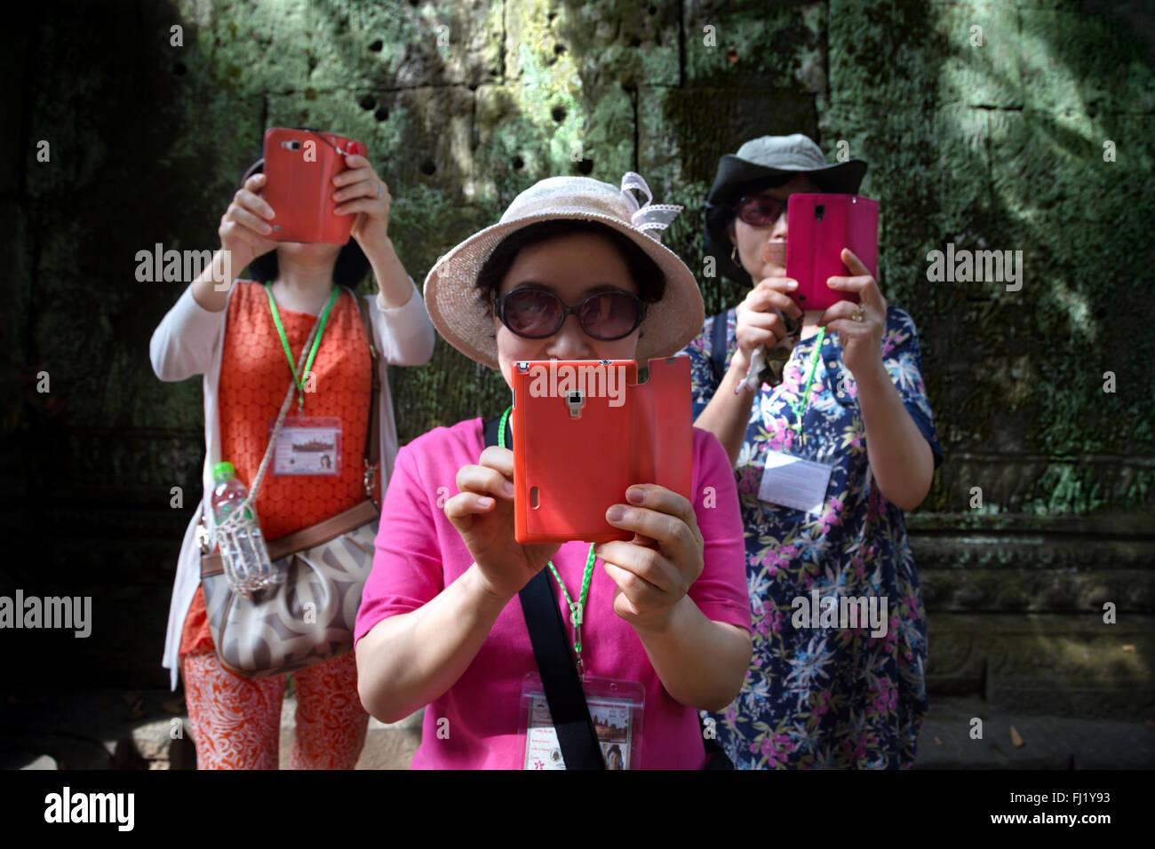 I turisti tenendo selfie con telefono cellulare all'interno di Angkor Vat tempio, Cambogia Immagini Stock