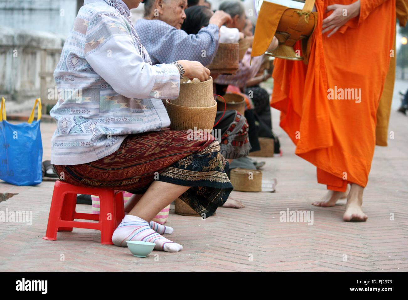 Tak Bat cerimonia al mattino - I monaci buddisti ricevere riso e cibo dalla popolazione in a Luang Prabang, Laos, Immagini Stock