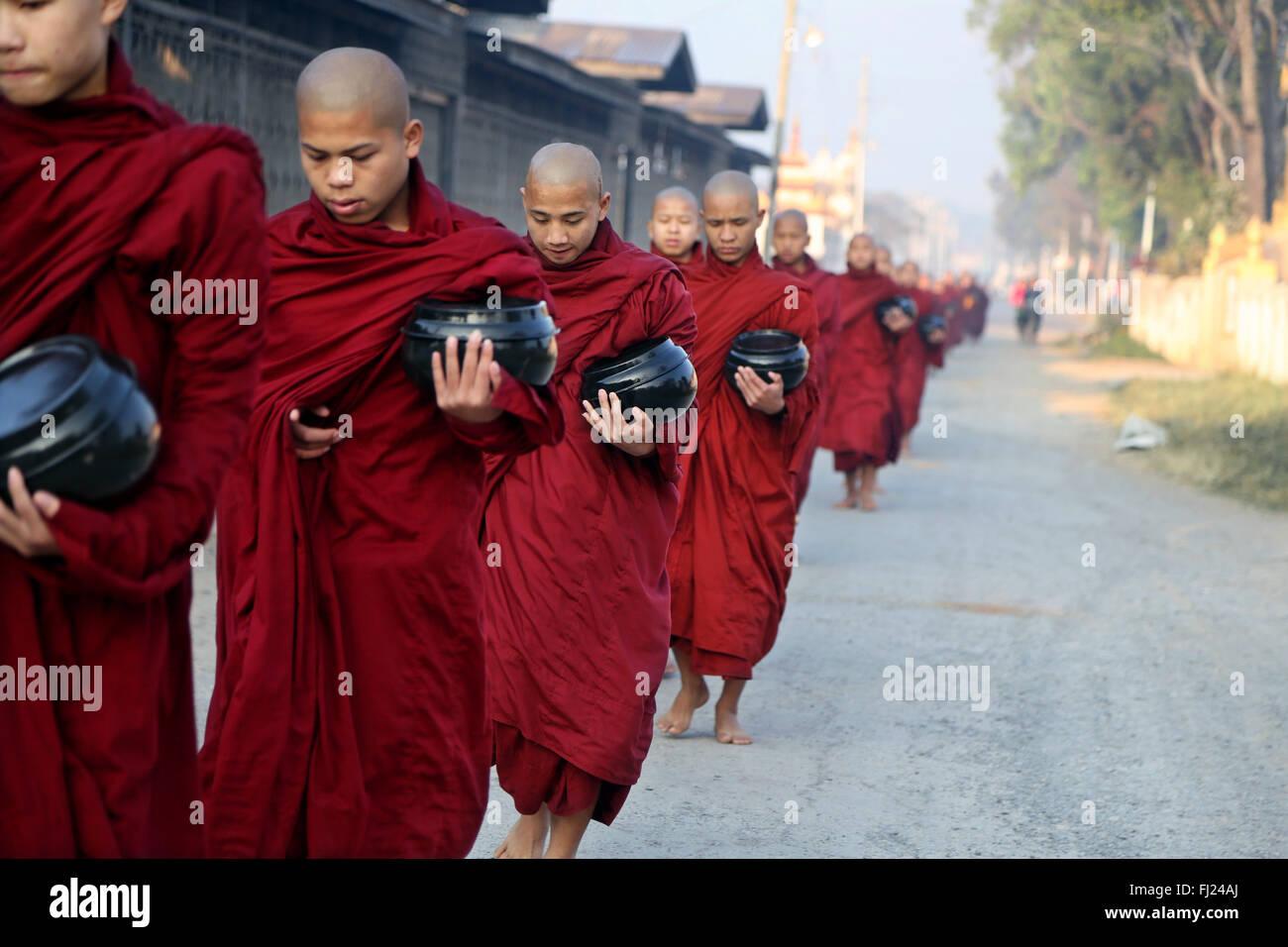 I monaci buddisti ricevere riso dalla popolazione, rituale giornaliero, Nyaung-U, Myanmar Immagini Stock