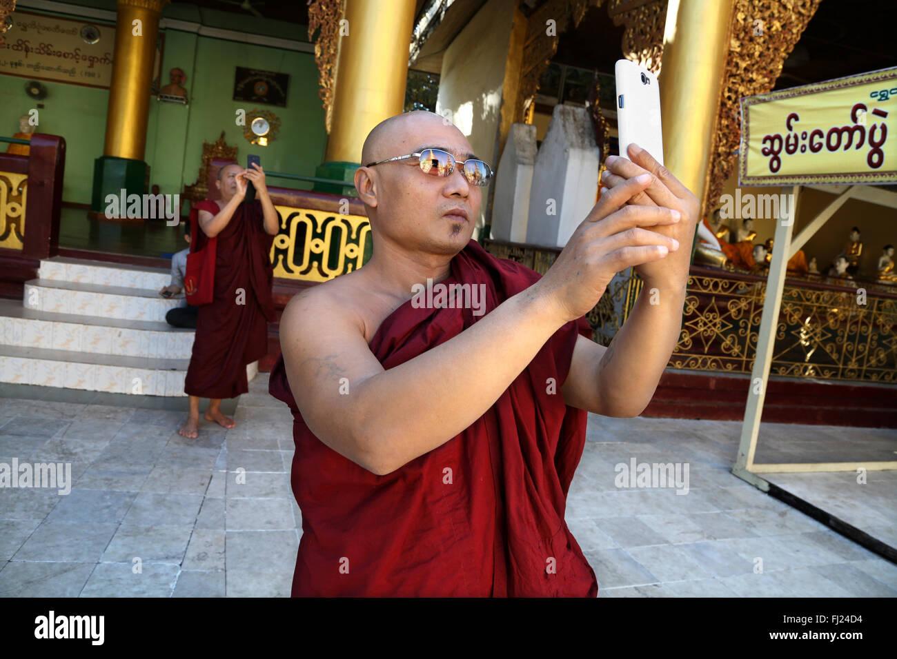 Monaco buddista tenendo selfie con telefono in Shwedagon pagoda, Rangoon, Myanmar Immagini Stock