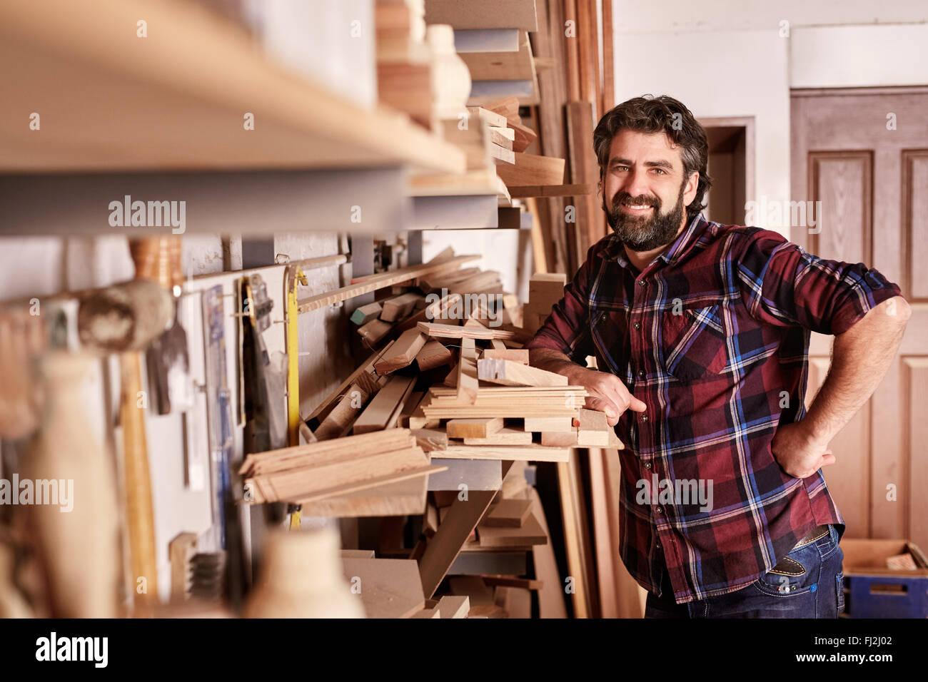 La falegnameria titolare di azienda in piedi sorridente nel suo laboratorio Immagini Stock