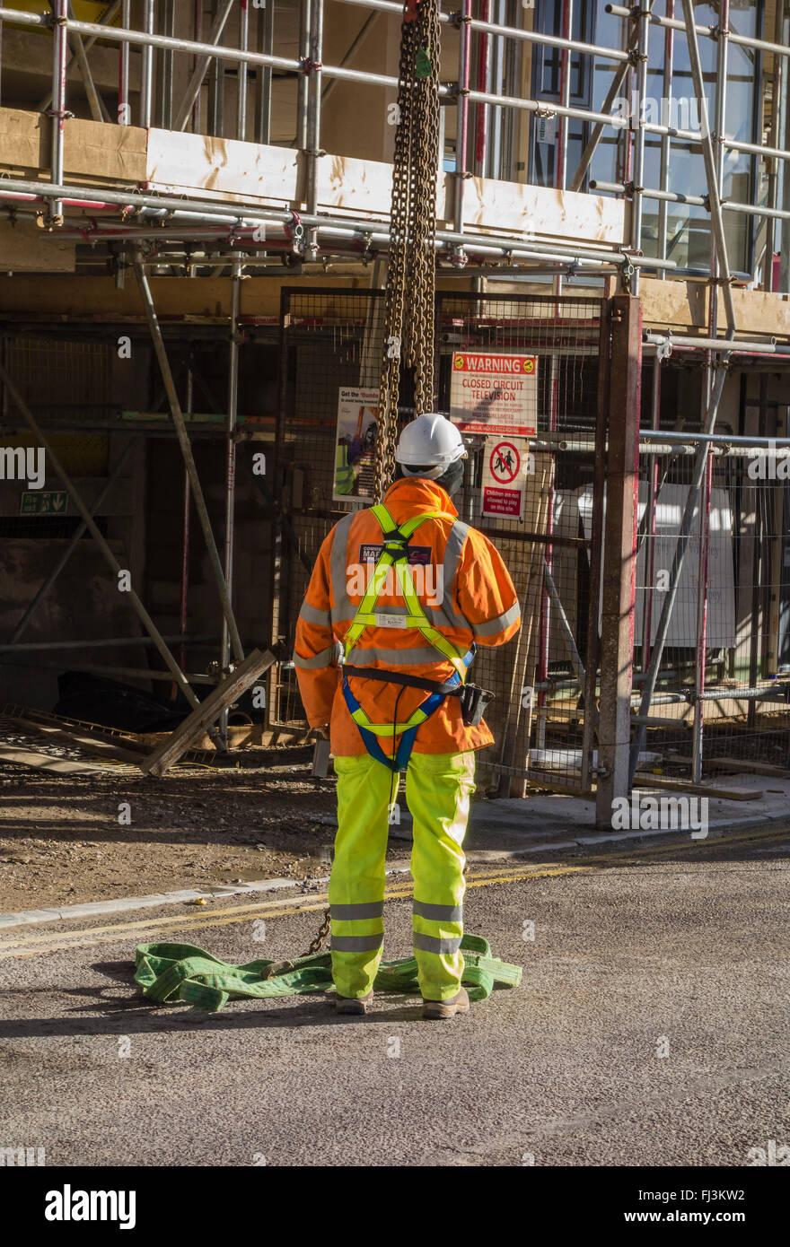 Lavoratore edile con casco di sicurezza in piedi al di sotto di un paranco al di fuori di un ponteggio sul nuovo Immagini Stock