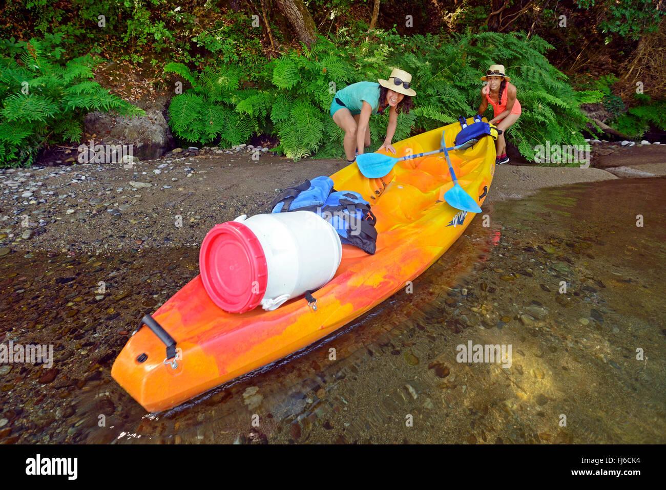 Due donne tirando i loro kayak fuori del fiume Golo, Francia, Corsica, Bastia Immagini Stock