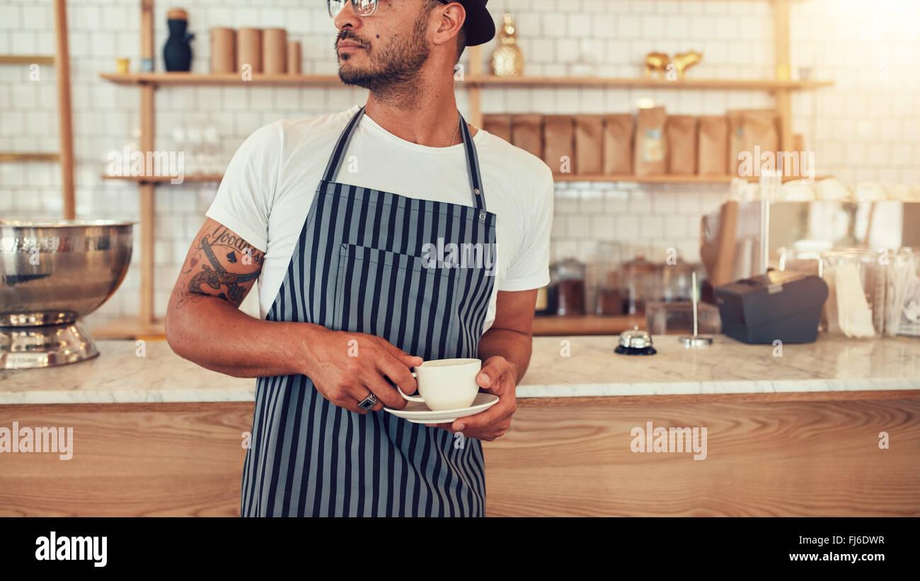Ritagliato Ritratto di giovane uomo in piedi presso il cafe contatore e guardando lontano. Maschio a lavorare in Immagini Stock