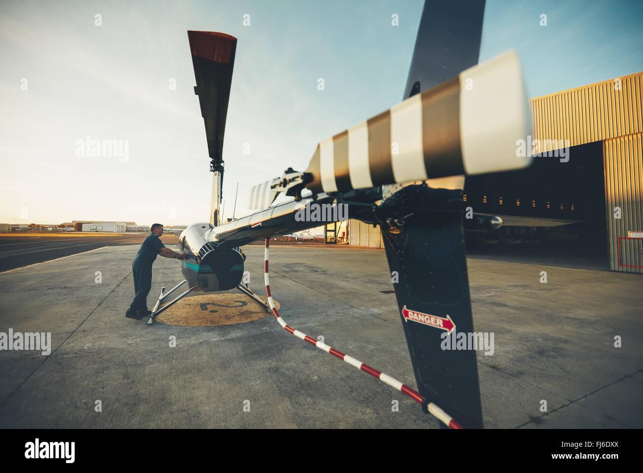 Maschio di pilota di elicottero di ispezione prima del decollo. Pilota di preparare il suo elicottero per il volo Immagini Stock