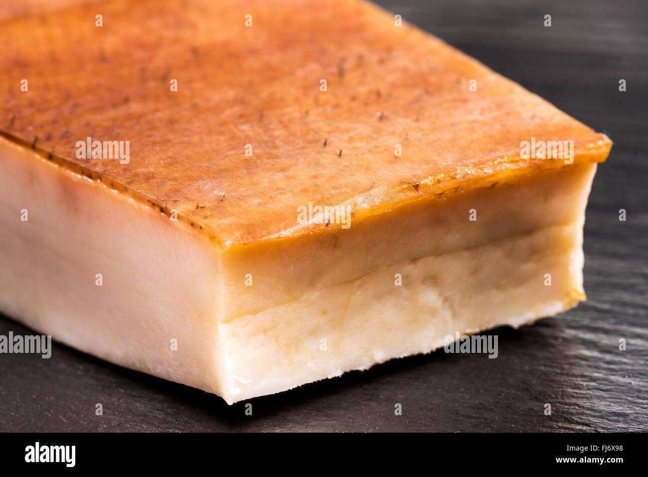 Pancetta di grasso su uno sfondo nero, Bill, pancetta di maiale, cotenna, affumicato, pelle, calorie, dieta, sapore, Immagini Stock
