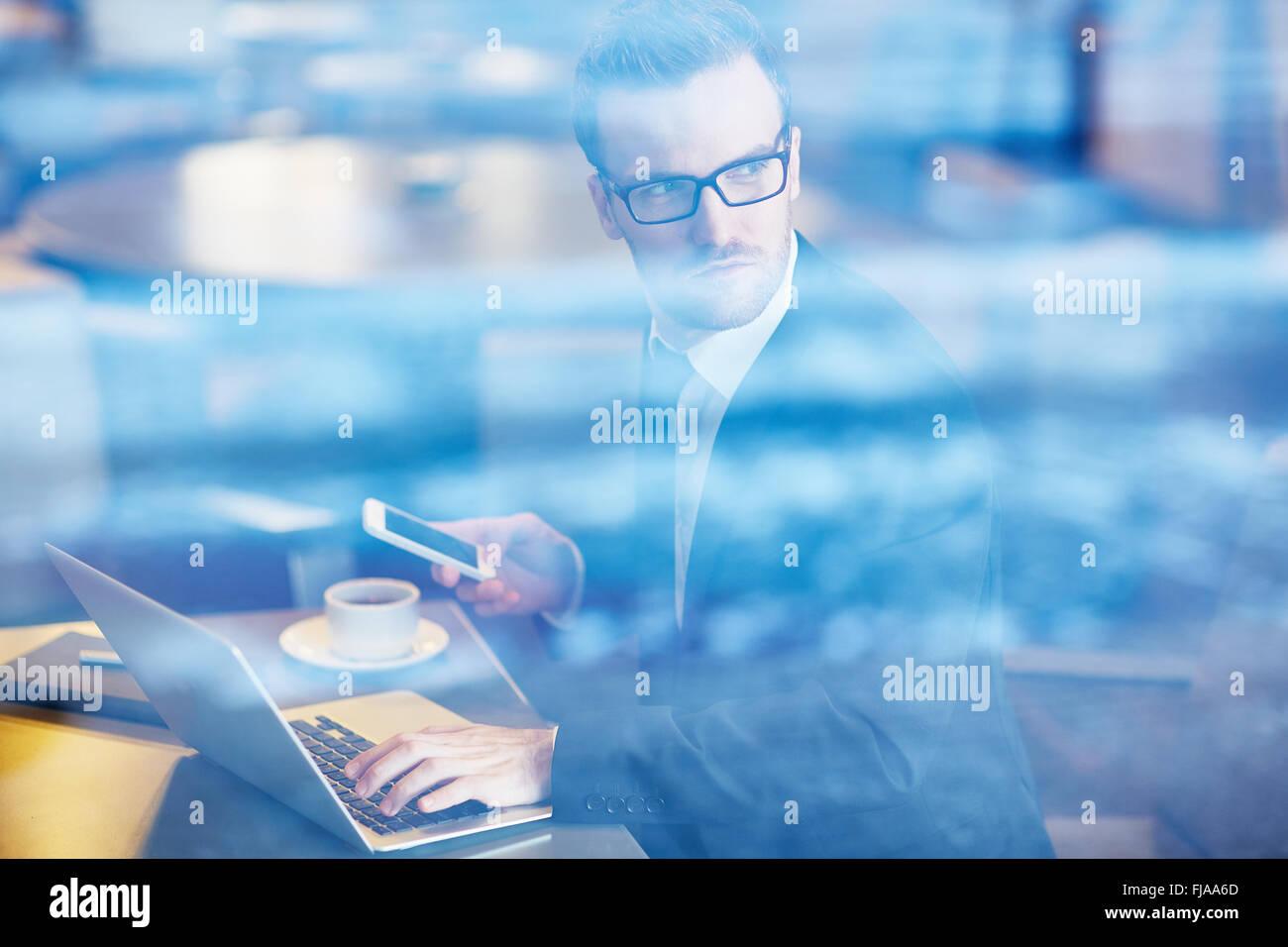 Grave dipendente con il cellulare digitando su laptop Immagini Stock