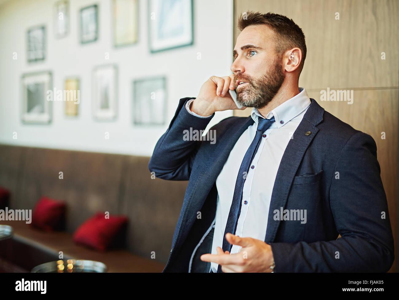 Giovane imprenditore parlando al telefono in ufficio Immagini Stock