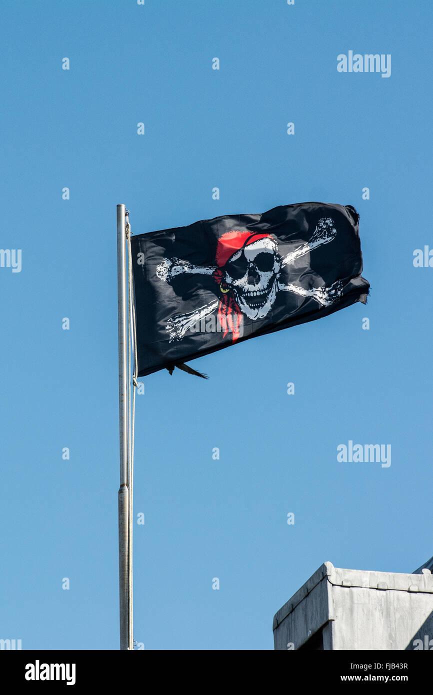 Jolly Roger bandiera pirata vola sopra il castello di Baltimora in West Cork in Irlanda Immagini Stock
