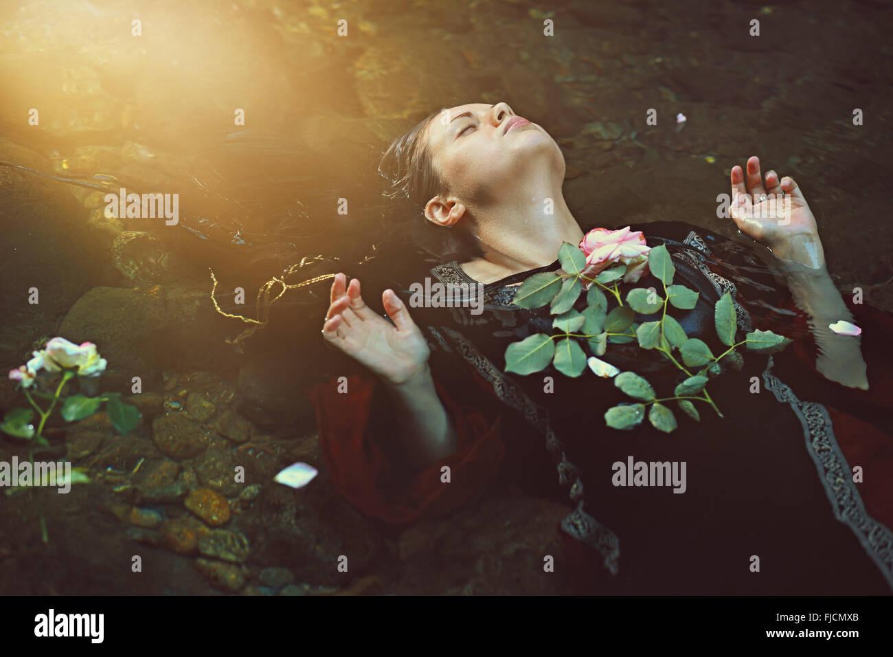 La donna nel buio del flusso di acqua e morbida luce del sole . Romantico e tragedia Immagini Stock