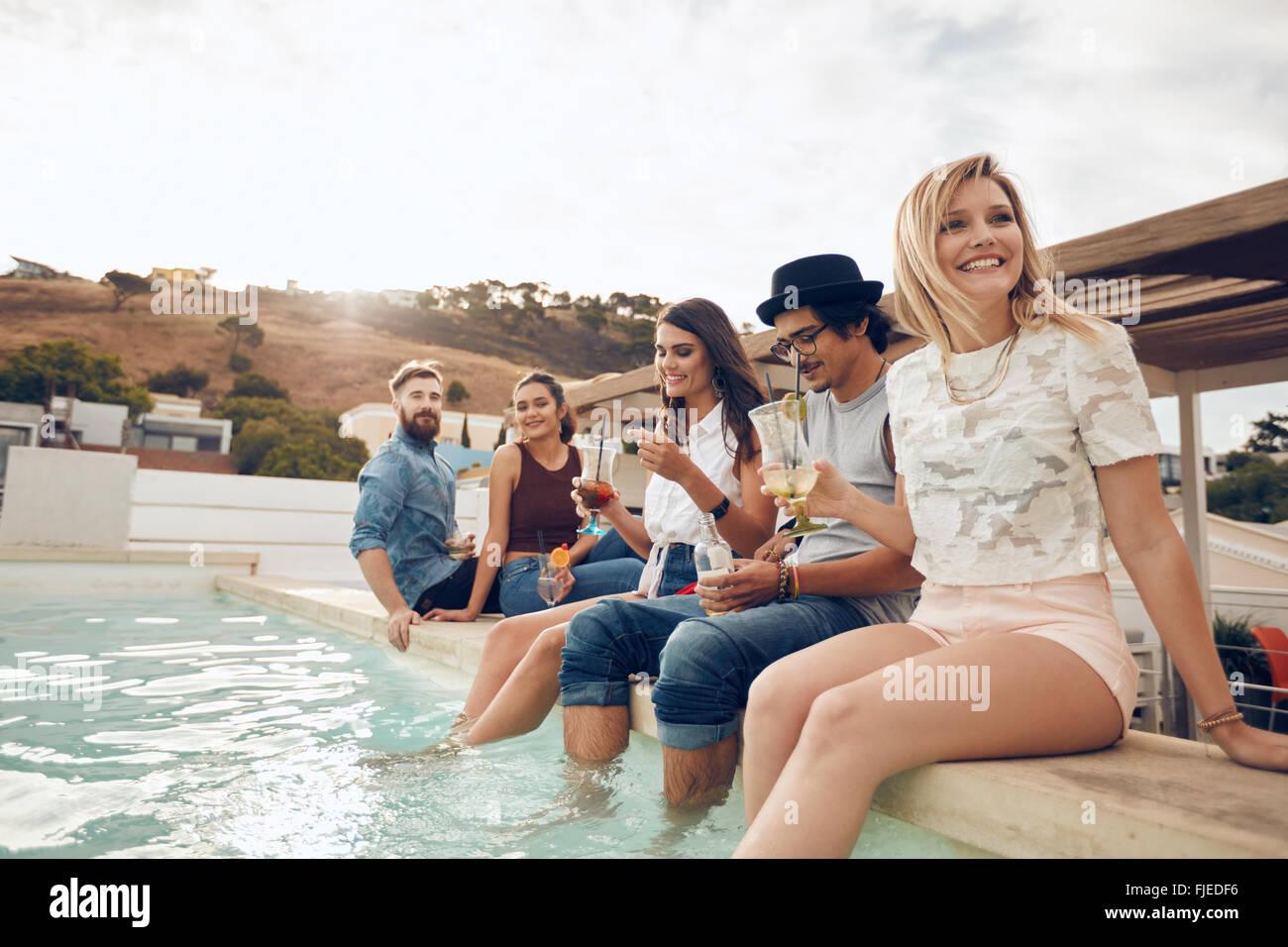 Multi-etnico gruppo di giovani appendere fuori dalla piscina azienda cocktail. Happy amici godendo party in piscina. Immagini Stock
