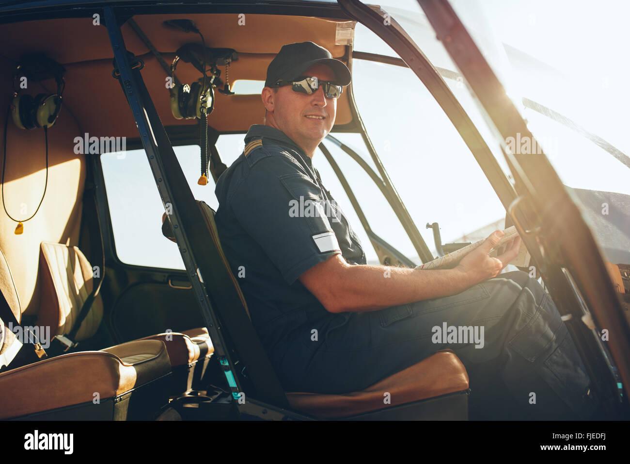 Ritratto di felice pilota maschile seduto in cabina di pilotaggio di un elicottero con una mappa per aviazione. Immagini Stock