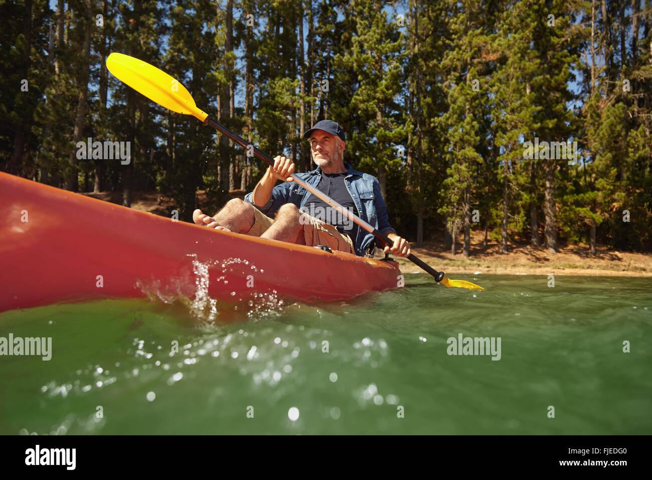 Ritratto di uomo maturo sguazzare un kayak in un lago. Senior uomo caucasico in canoa sul giorno di estate. Foto Stock