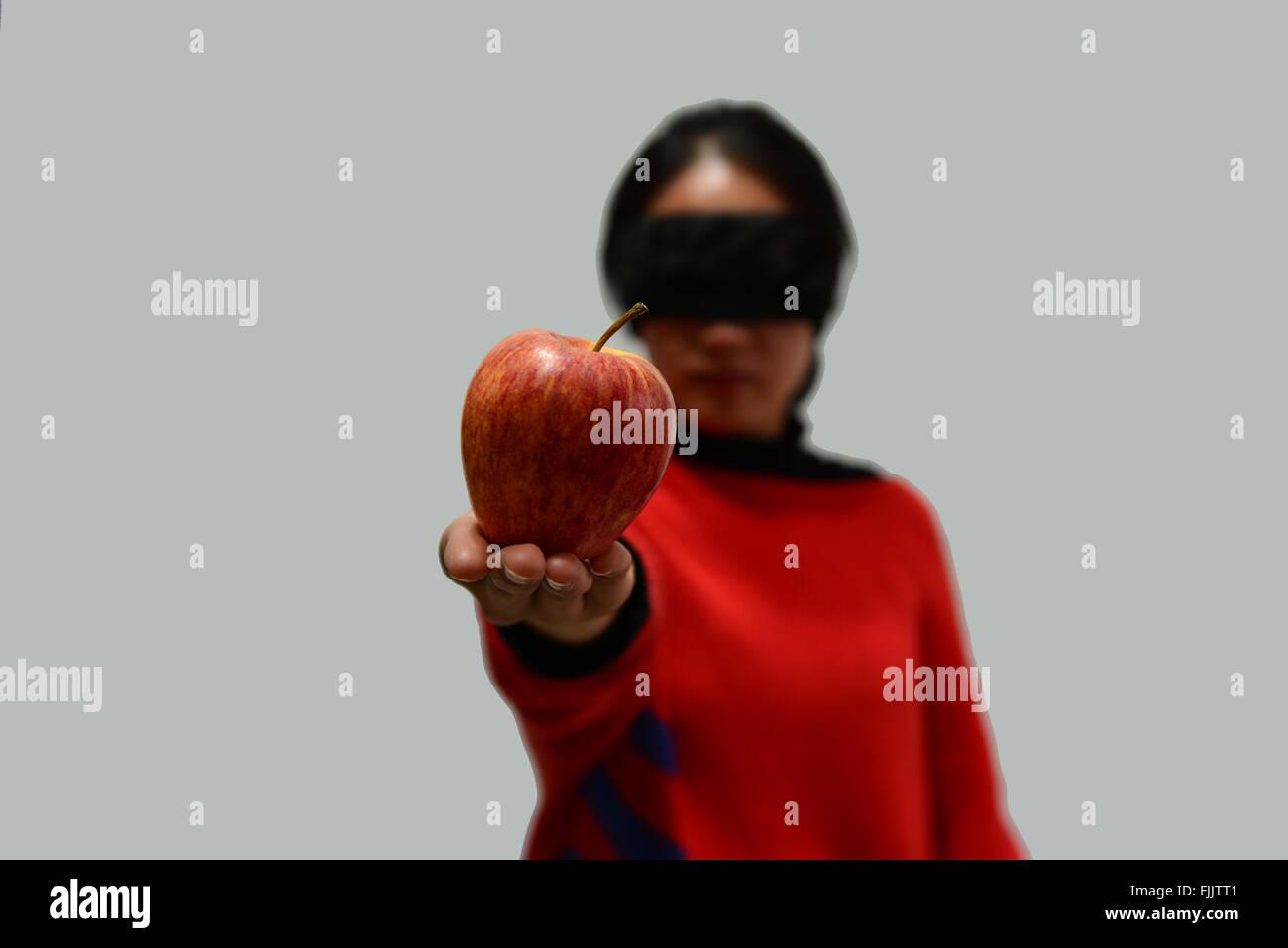 La donna gli occhi bendati su sfondo bianco e prendere un Apple Immagini Stock