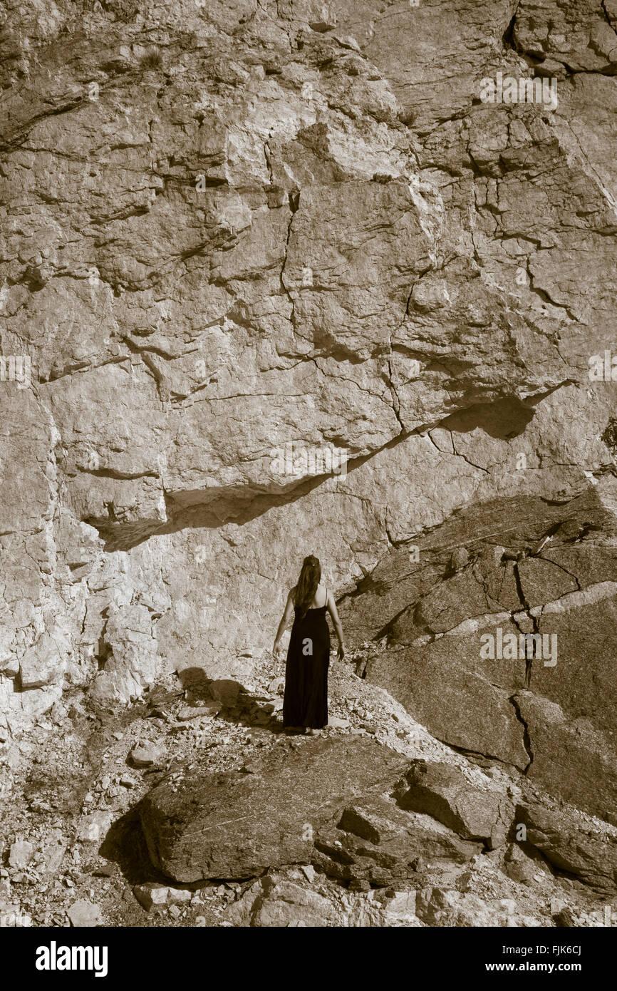 Vista posteriore della donna in piedi di fronte di roccia solida parete, Arizona, Stati Uniti. Di fronte a difficoltà, Immagini Stock