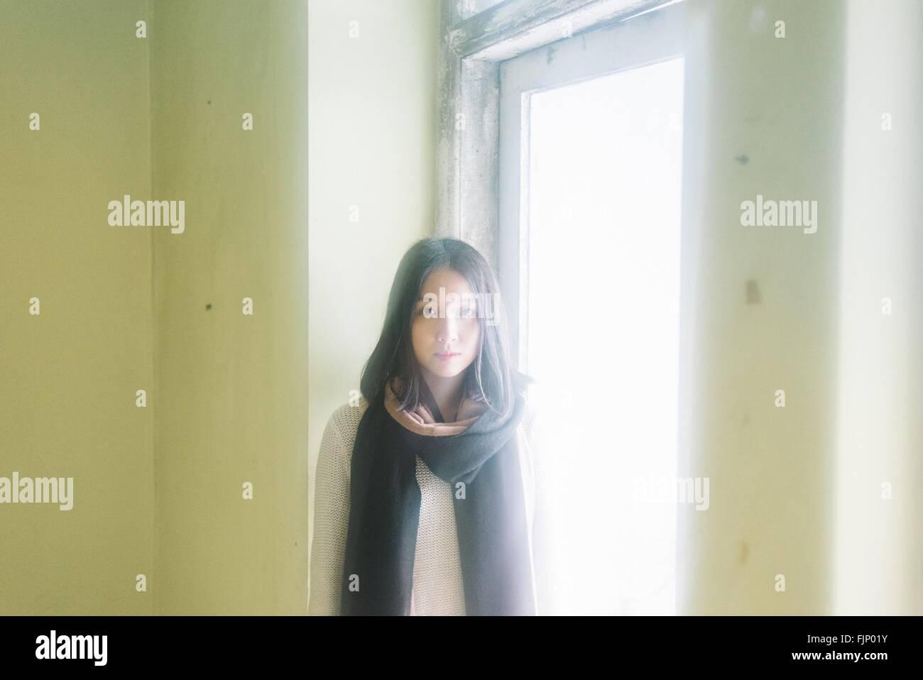 Ritratto di giovane donna in piedi dalla finestra a casa Immagini Stock