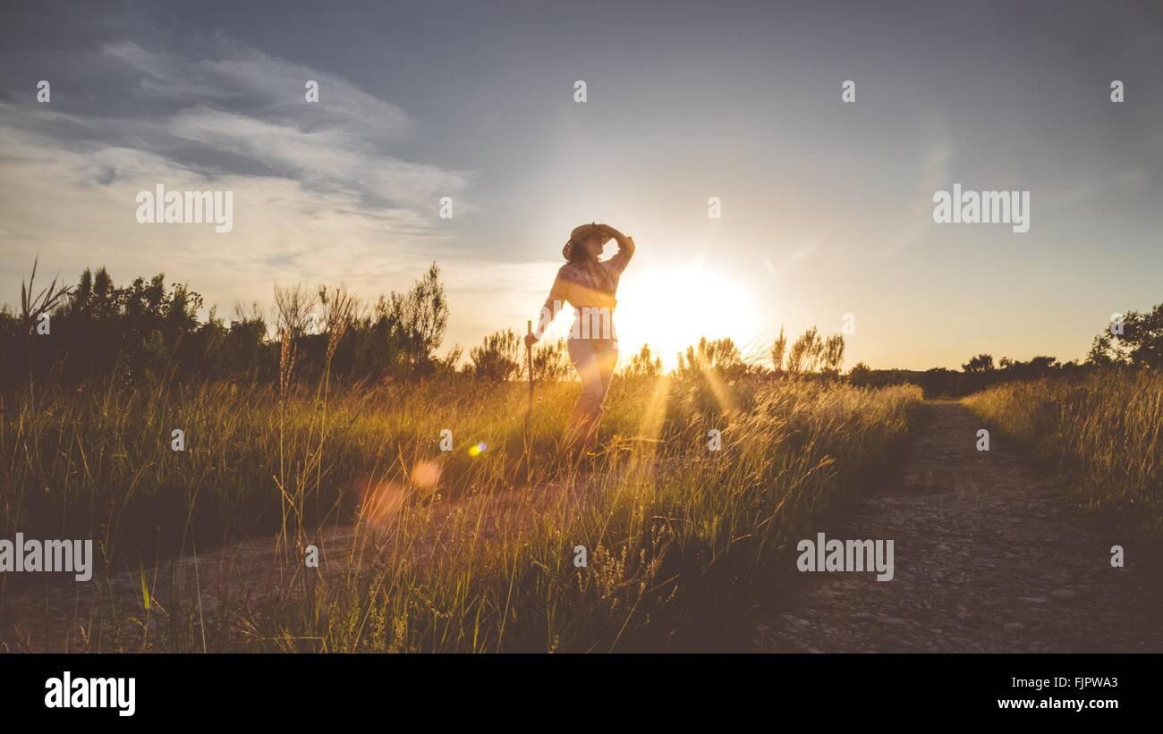 Donna in posa mentre si sta in piedi sul campo contro il cielo al tramonto Immagini Stock