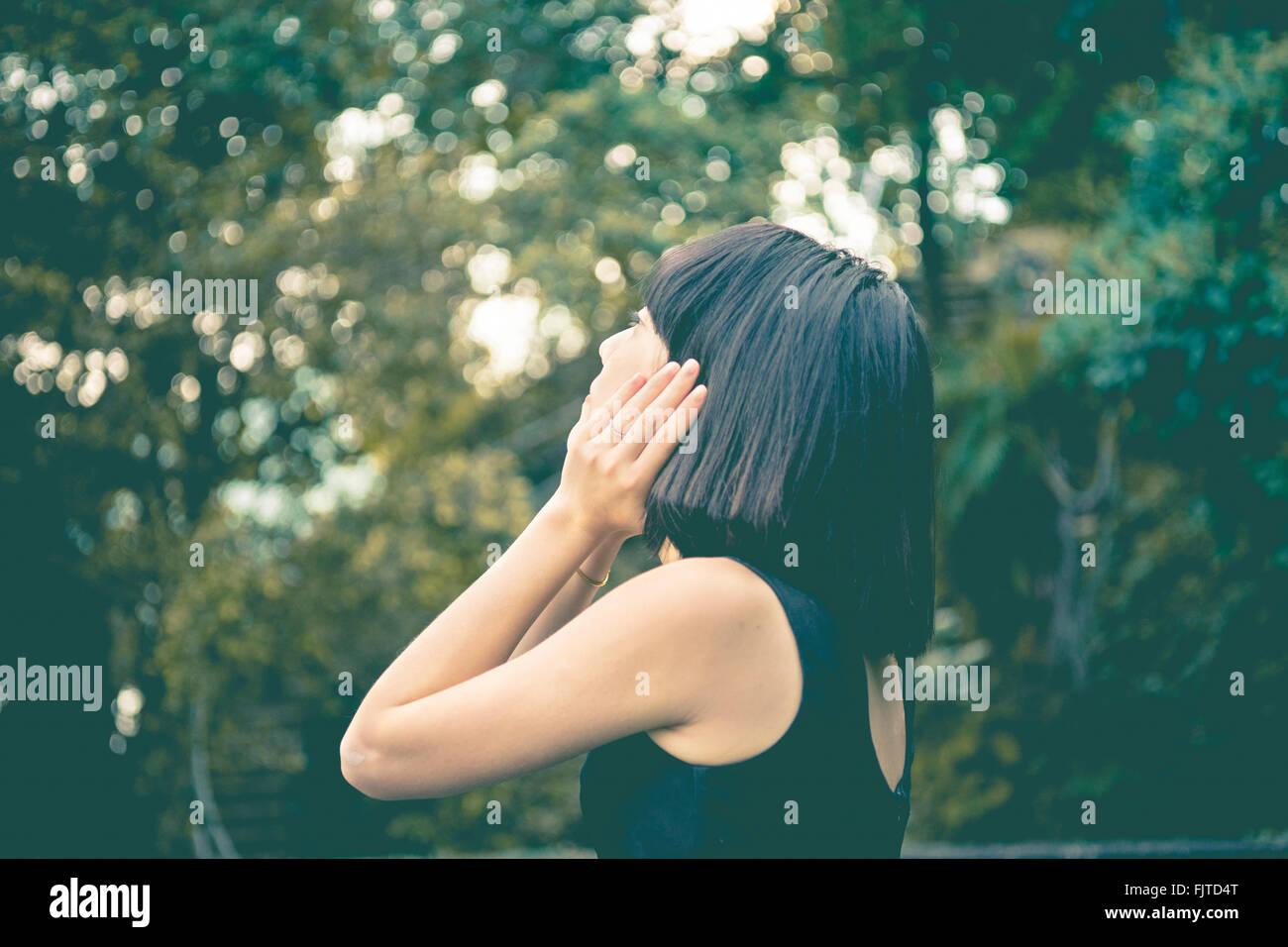 In primo piano della donna che guarda lontano contro alberi Immagini Stock
