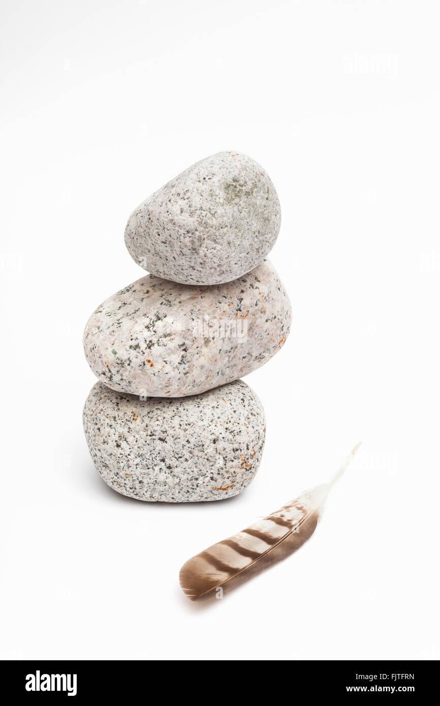 Un mucchio di pietre e una piuma Immagini Stock