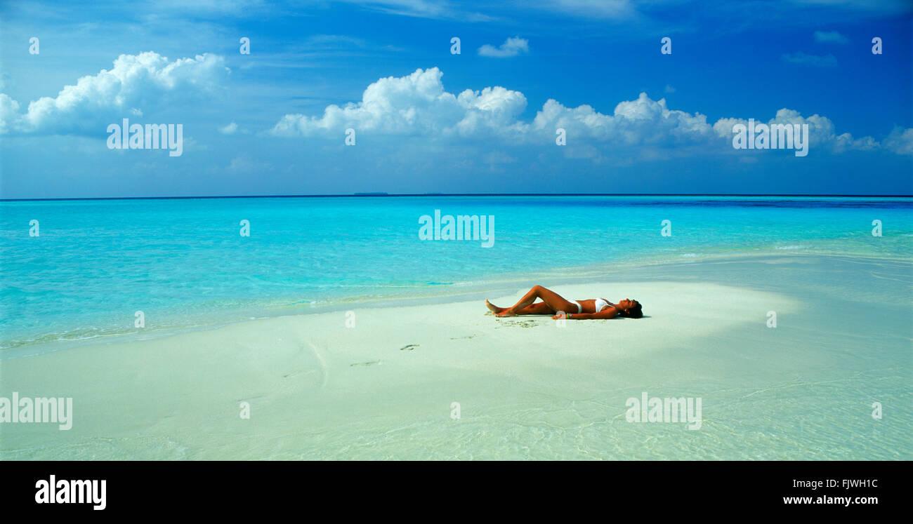 Panoramica della donna in appoggio sul sandbar durante le vacanze nella vostra isola preferita paradise Immagini Stock
