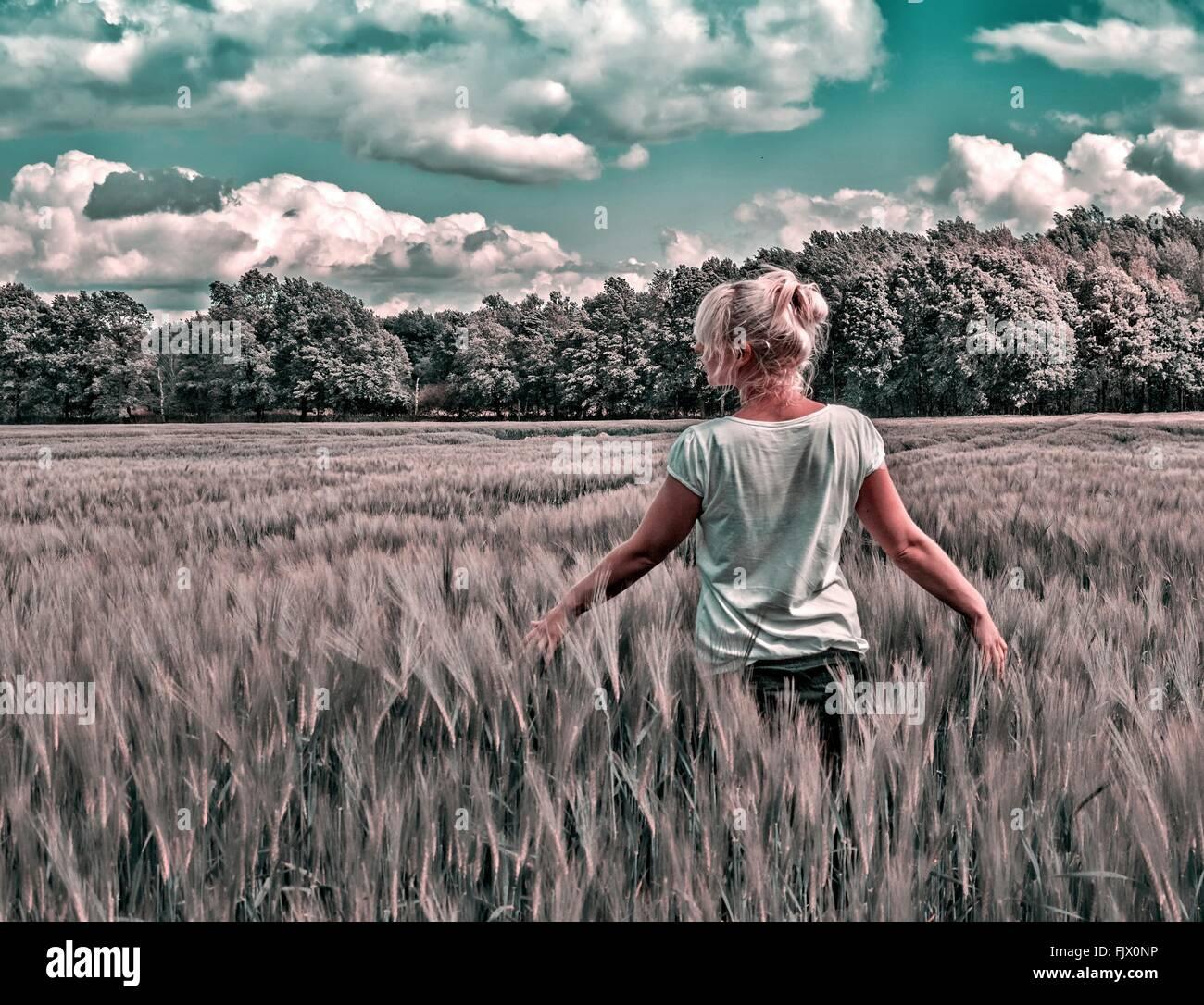 Vista posteriore della donna in piedi sul settore agricolo contro Sky Immagini Stock