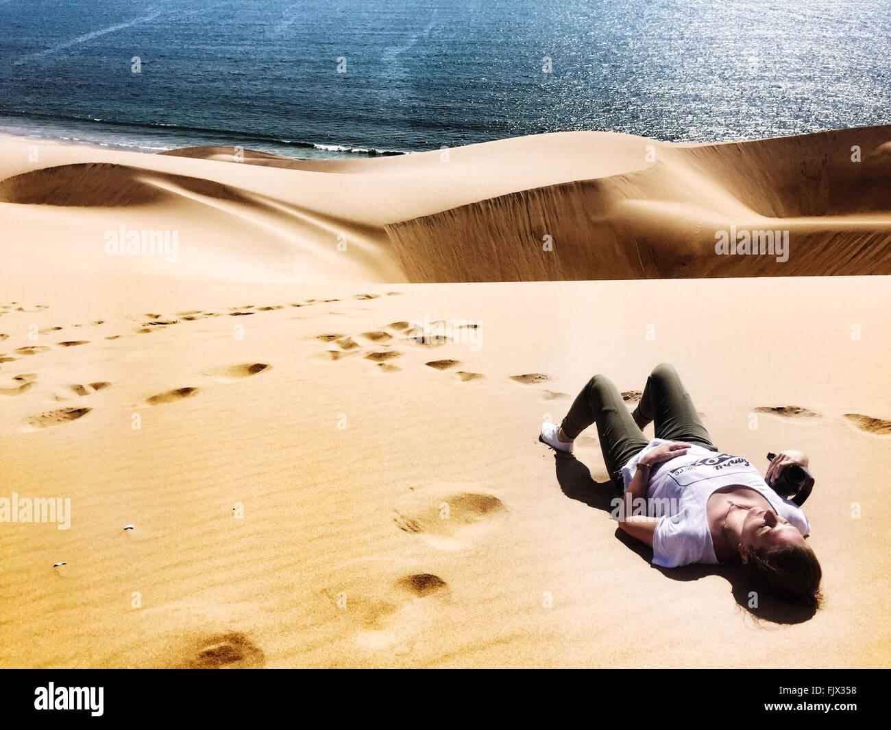 Elevato angolo di visione della donna rilassante su deserto dal mare Immagini Stock