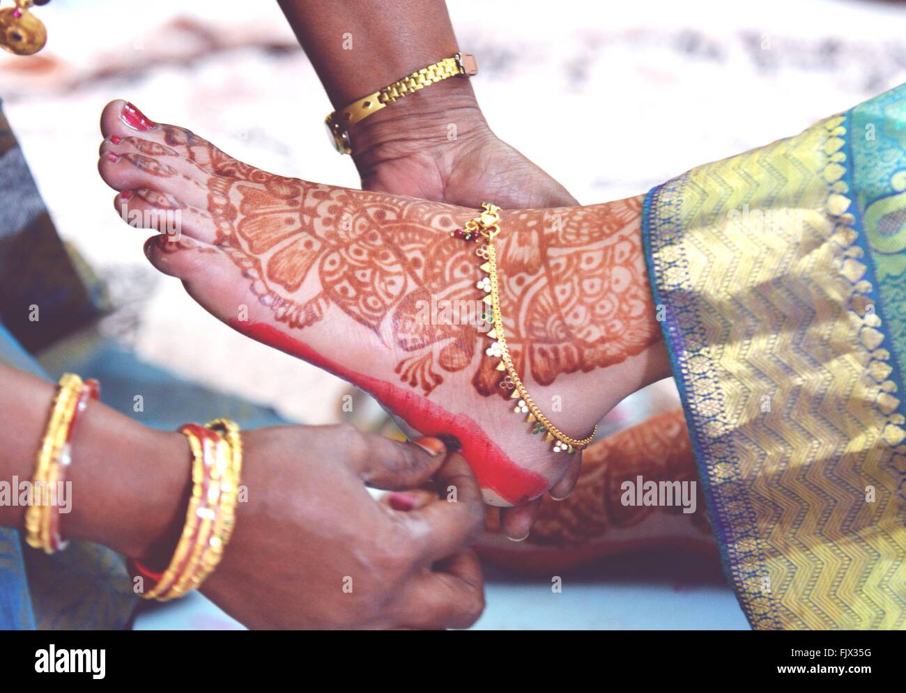 Immagine ritagliata della donna l'applicazione di alta colorante sul piede della sposa Immagini Stock