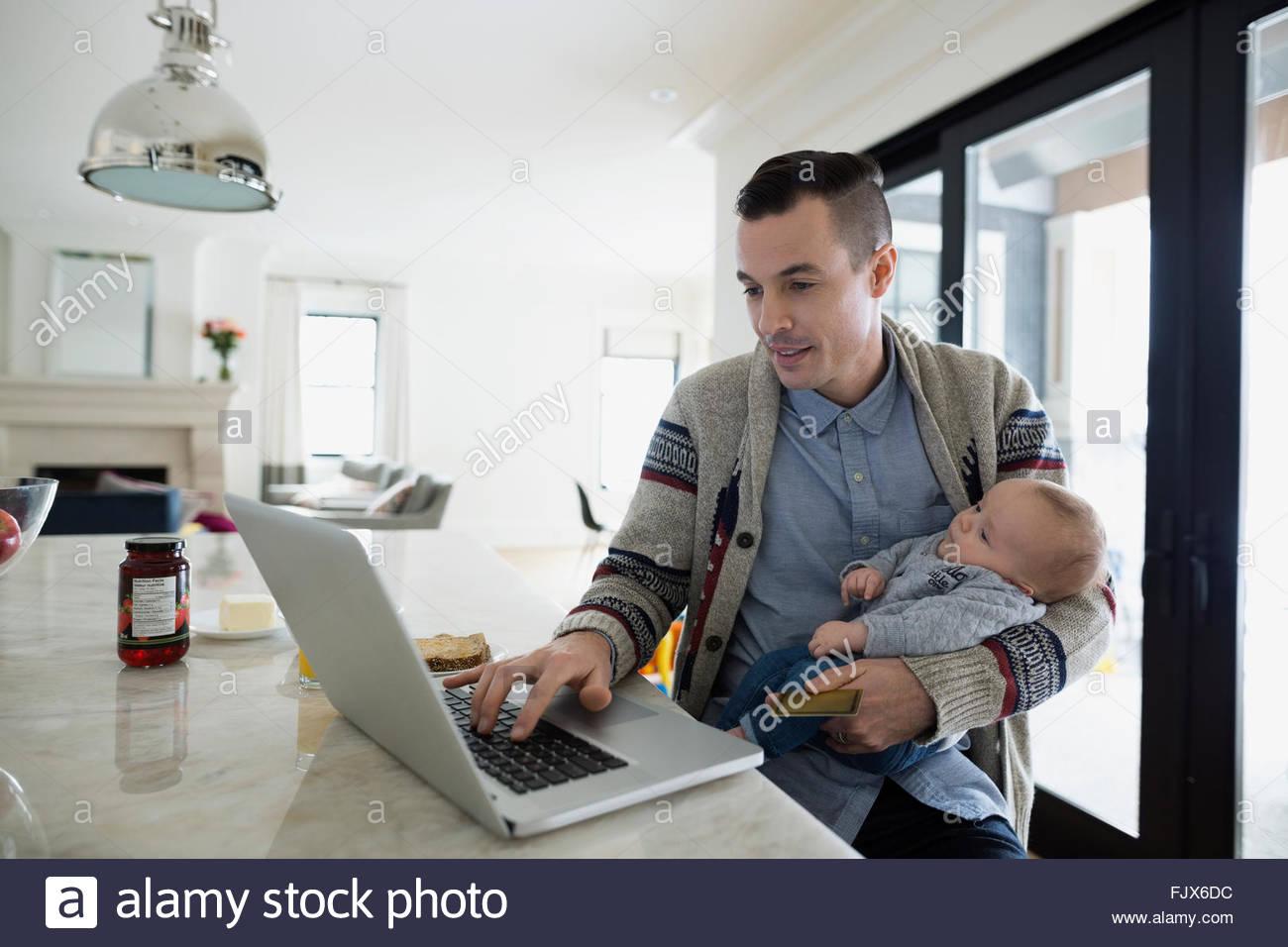 Padre holding baby figlio e lavorare al computer portatile Immagini Stock