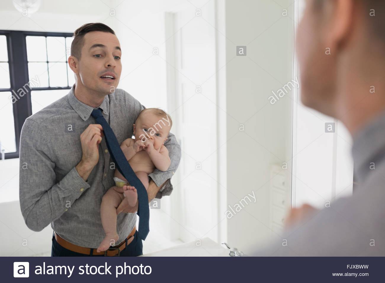 Padre di vestirsi di alimentazione figlio bambino con bottiglia Immagini Stock