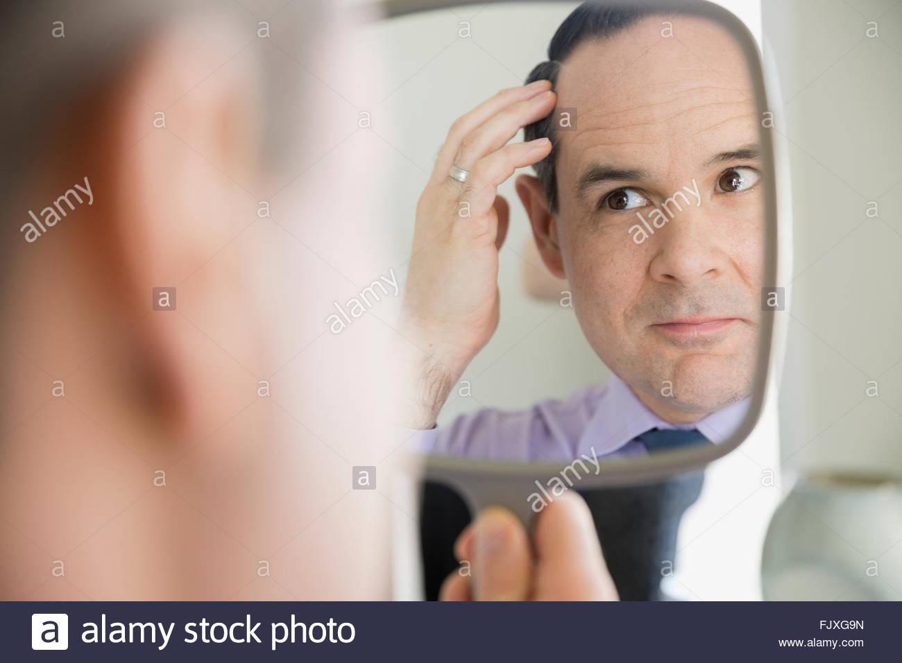 L'uomo controllare i capelli in mano lo specchio Immagini Stock