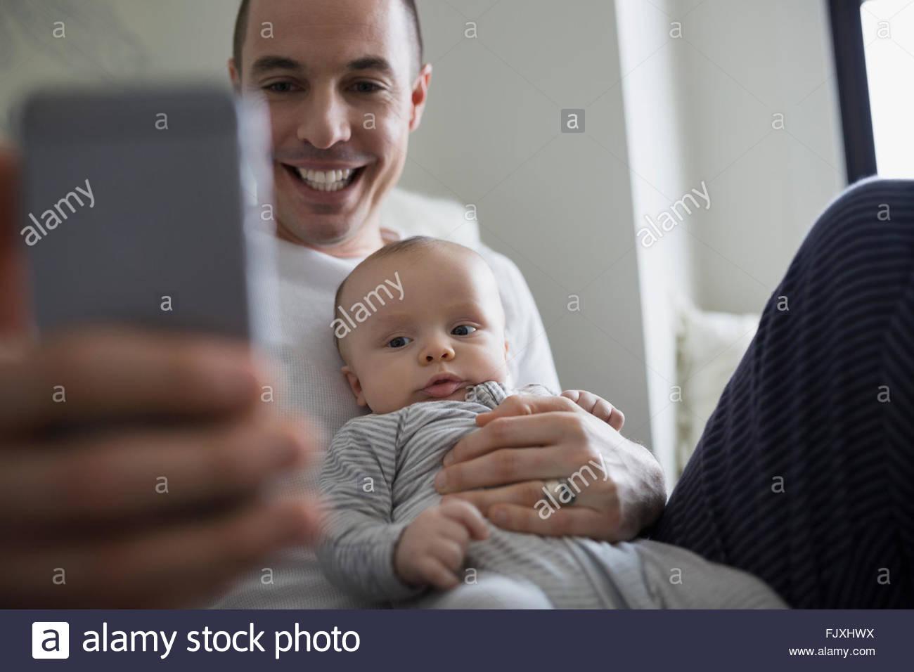 Sorridente padre e figlio bambino tenendo selfie Immagini Stock