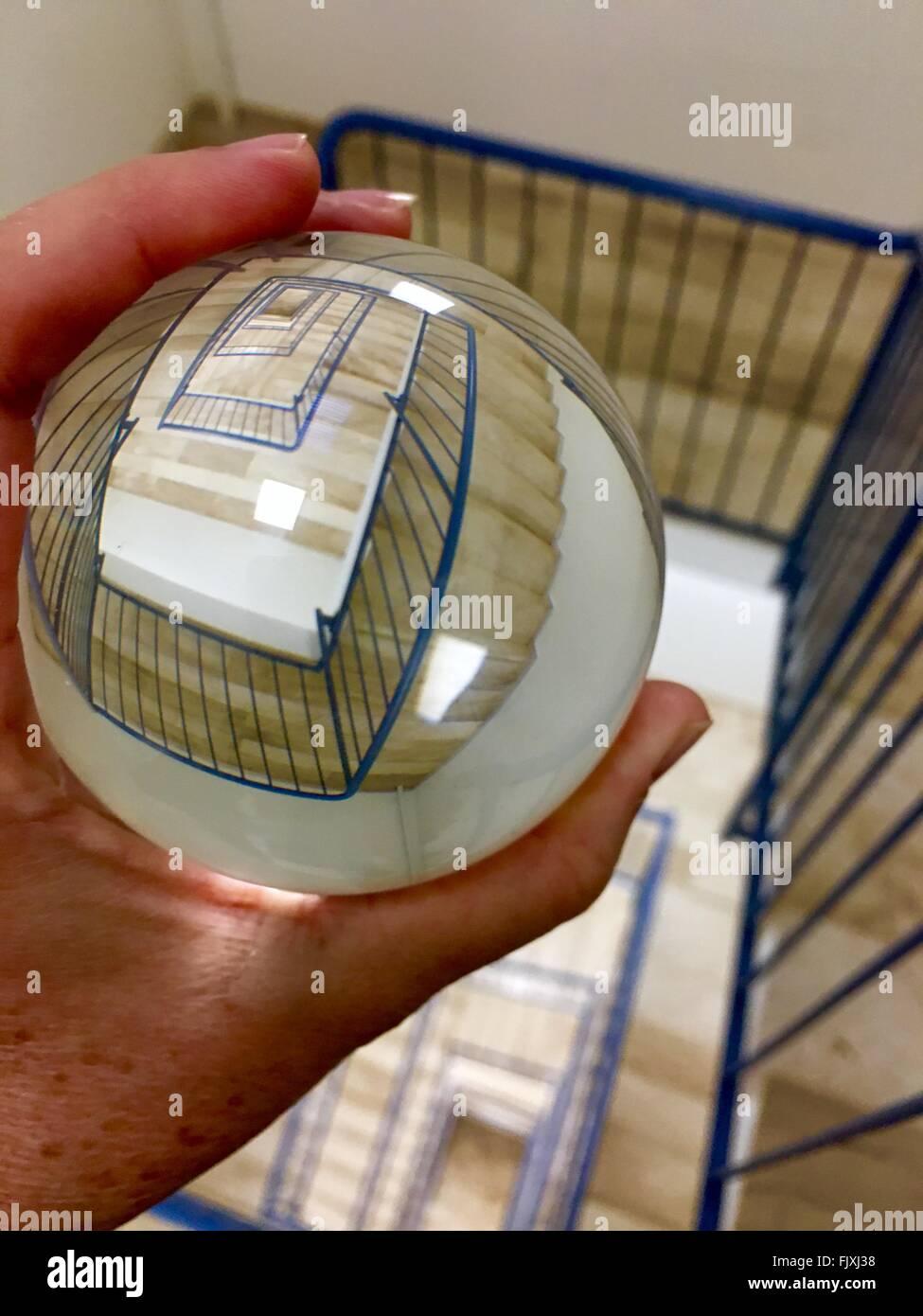 Immagine ritagliata della persona in possesso di palla di cristallo con la riflessione di una scalinata a spirale Immagini Stock