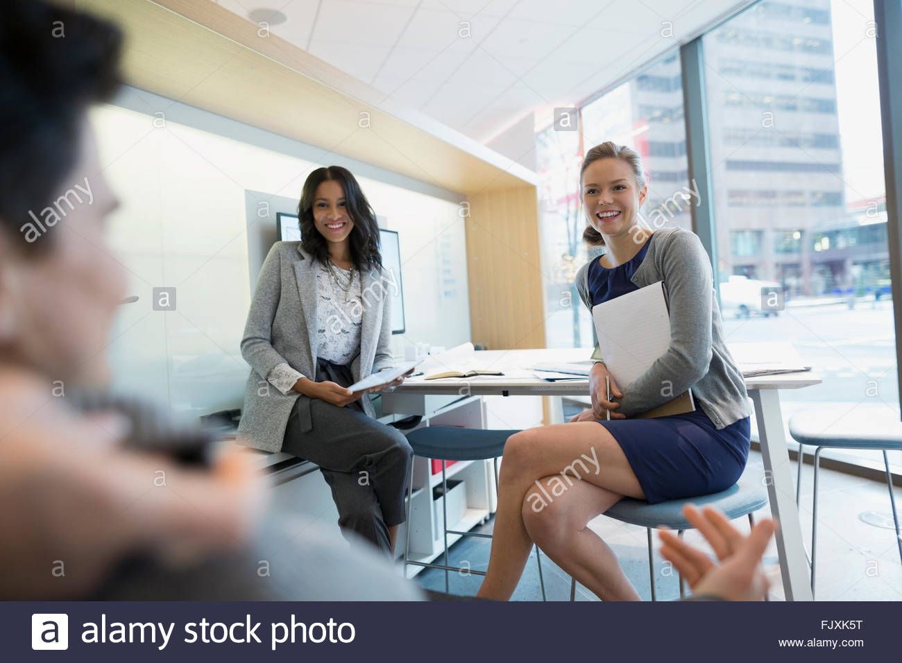 La gente di affari incontro alla scrivania in ufficio urbano Immagini Stock