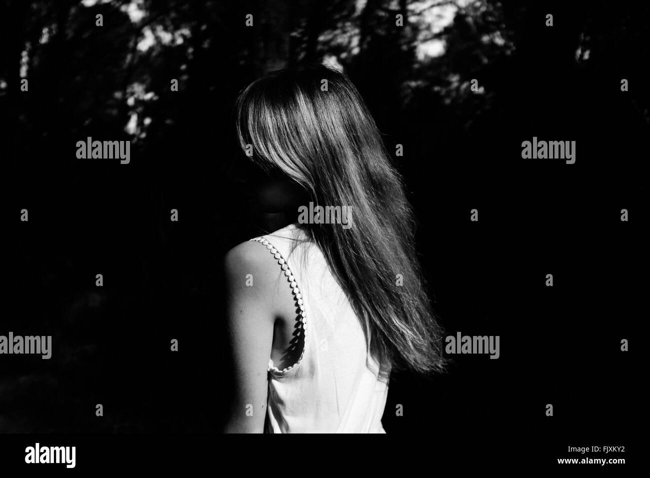Vista posteriore di una donna contro piante scuro Immagini Stock