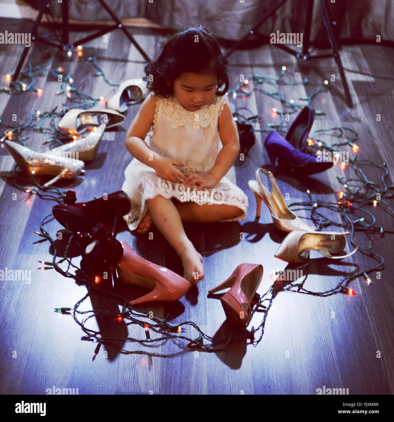 Ragazza seduta nel mezzo di tacchi alti e le luci di Natale sul pavimento di legno duro Immagini Stock