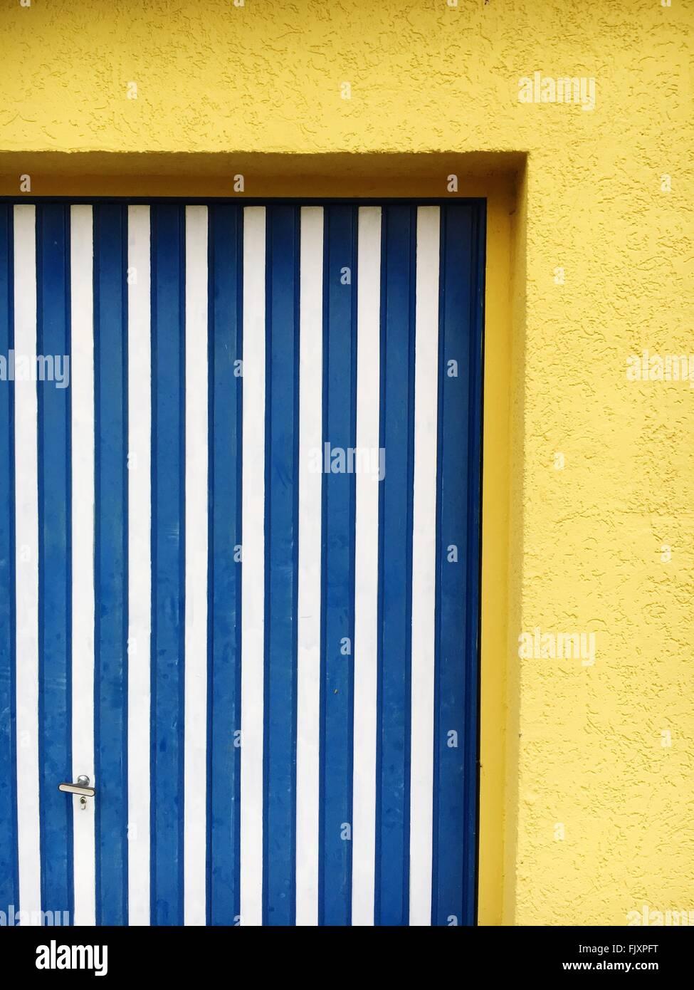A strisce blu sulla porta di casa gialla Immagini Stock