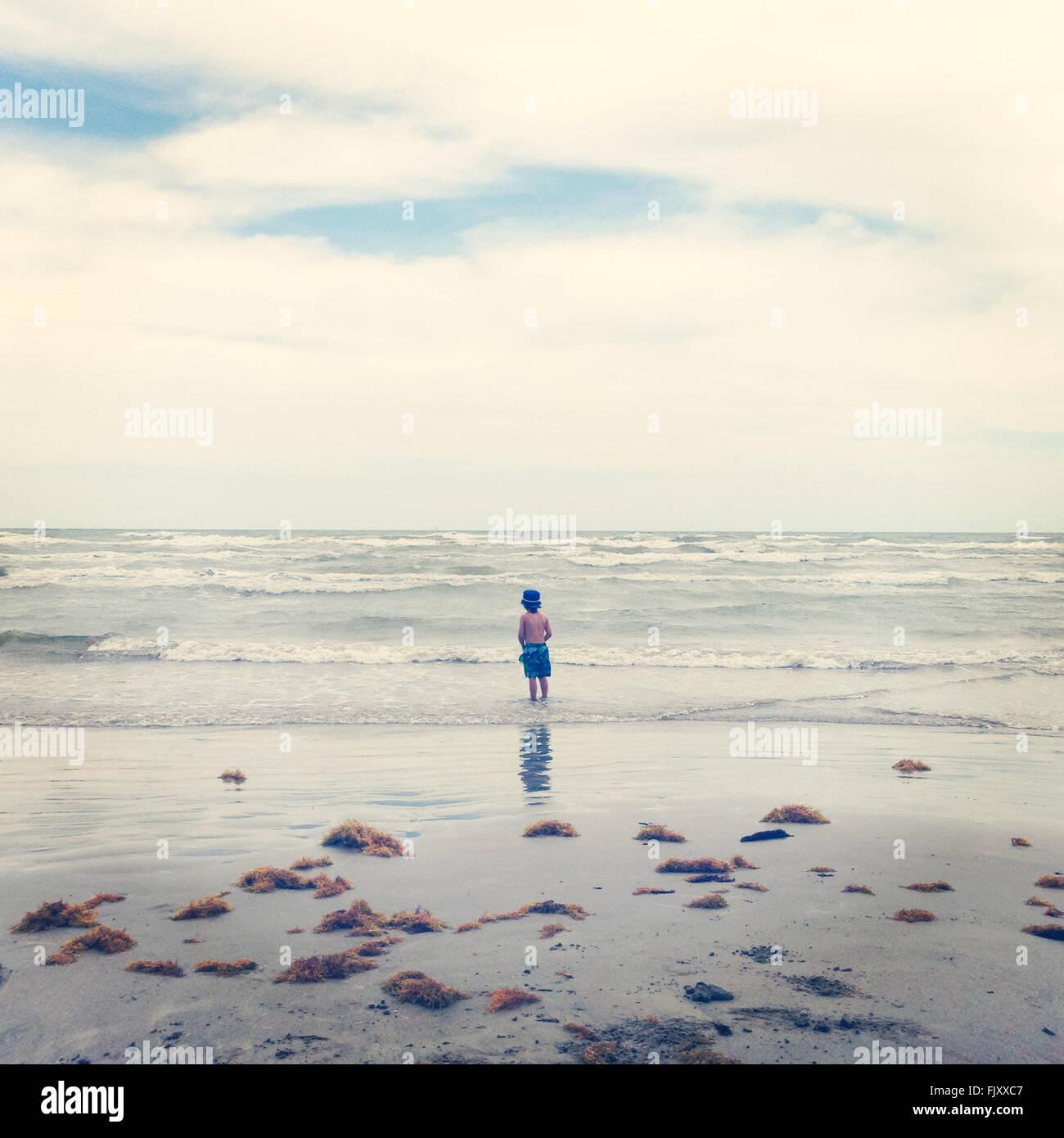 Vista posteriore del ragazzo Shirtless permanente al mare contro il cielo nuvoloso Immagini Stock