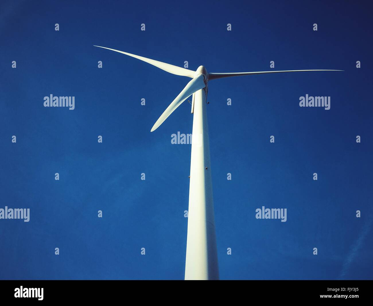 Basso angolo vista della turbina eolica contro il cielo blu Immagini Stock