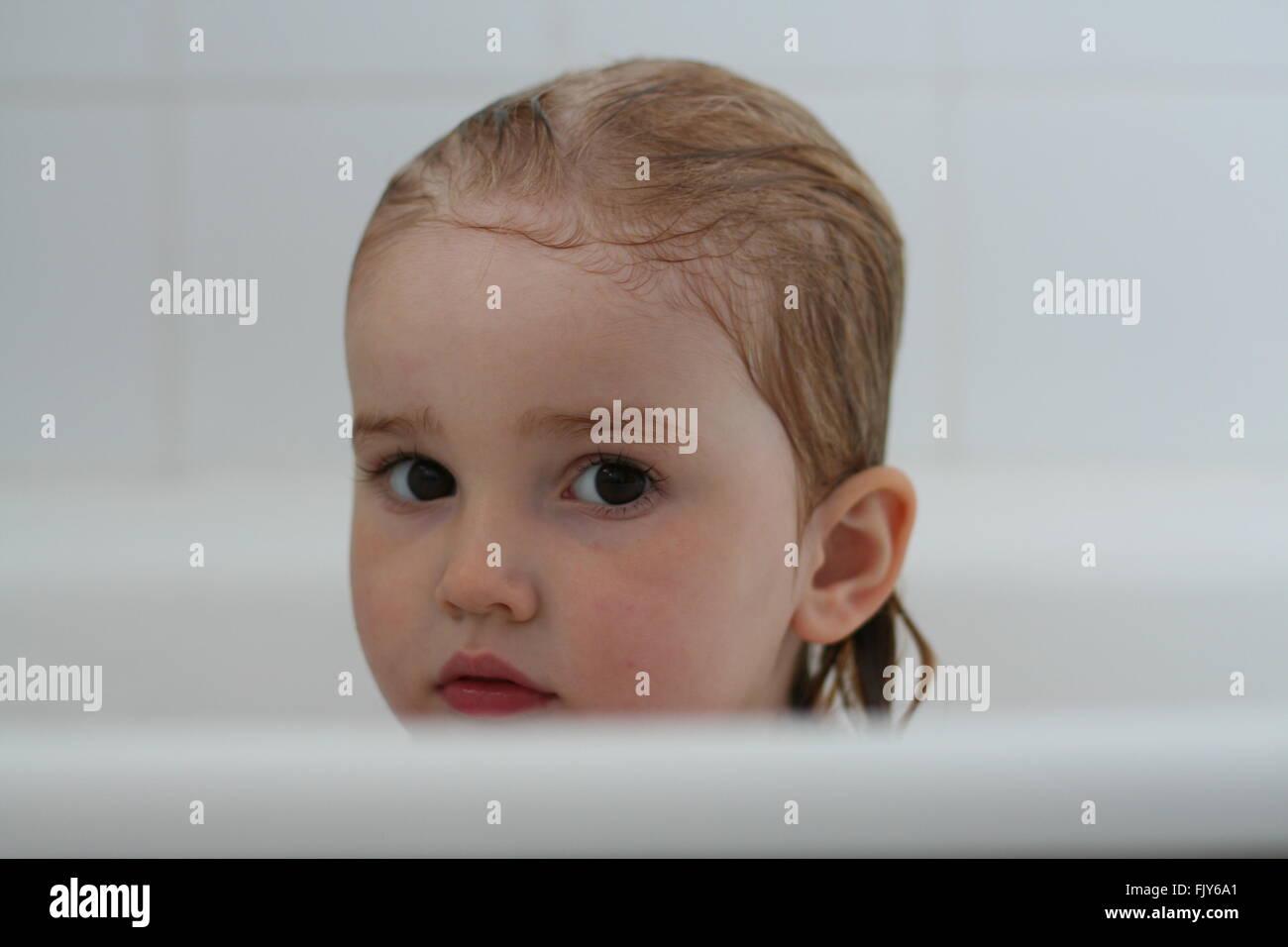 Bambina bambino seduto in un bagno di colore bianco con i capelli