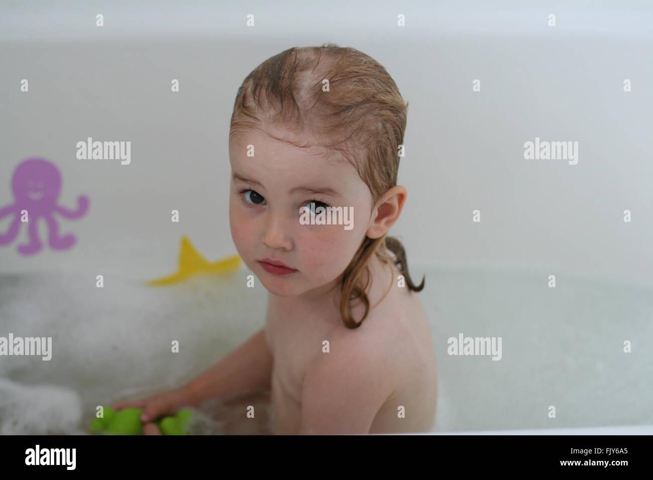 Bambina bambino seduto in un bagno di colore bianco con capelli