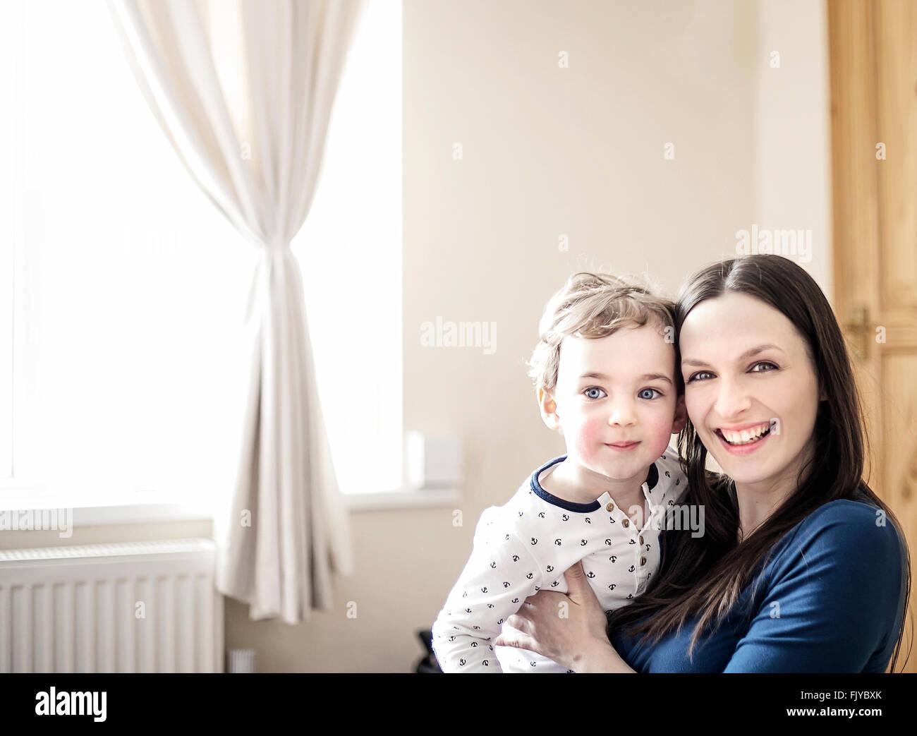 Giovane mamma con il suo piccolo ragazzo in armi a casa Immagini Stock