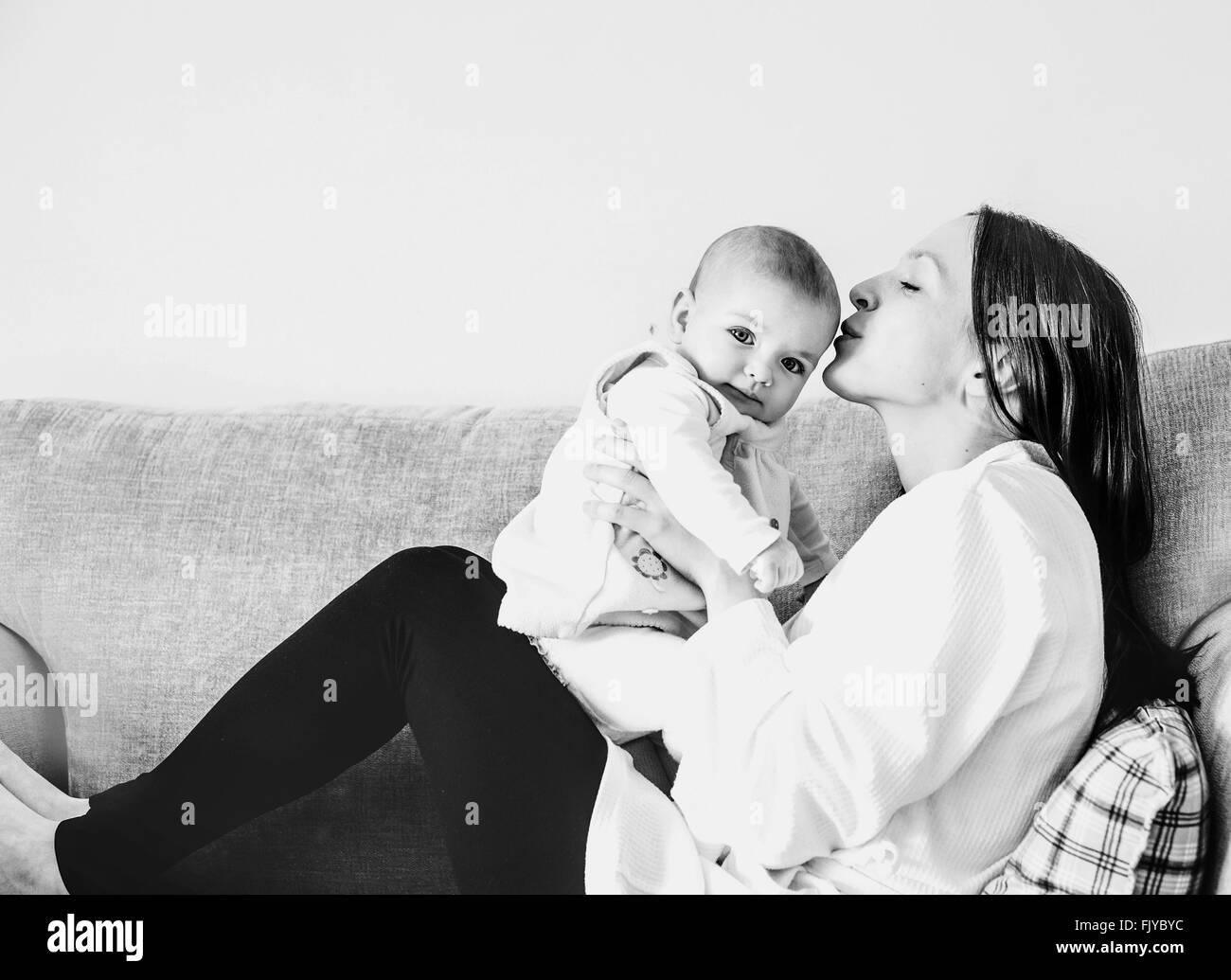 Giovane mamma baciando la sua bambina sul divano di casa Immagini Stock