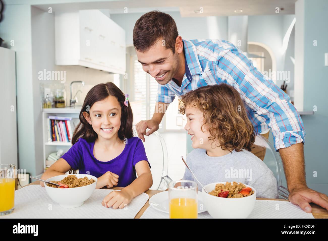 Uomo felice con bambini aventi la prima colazione Immagini Stock