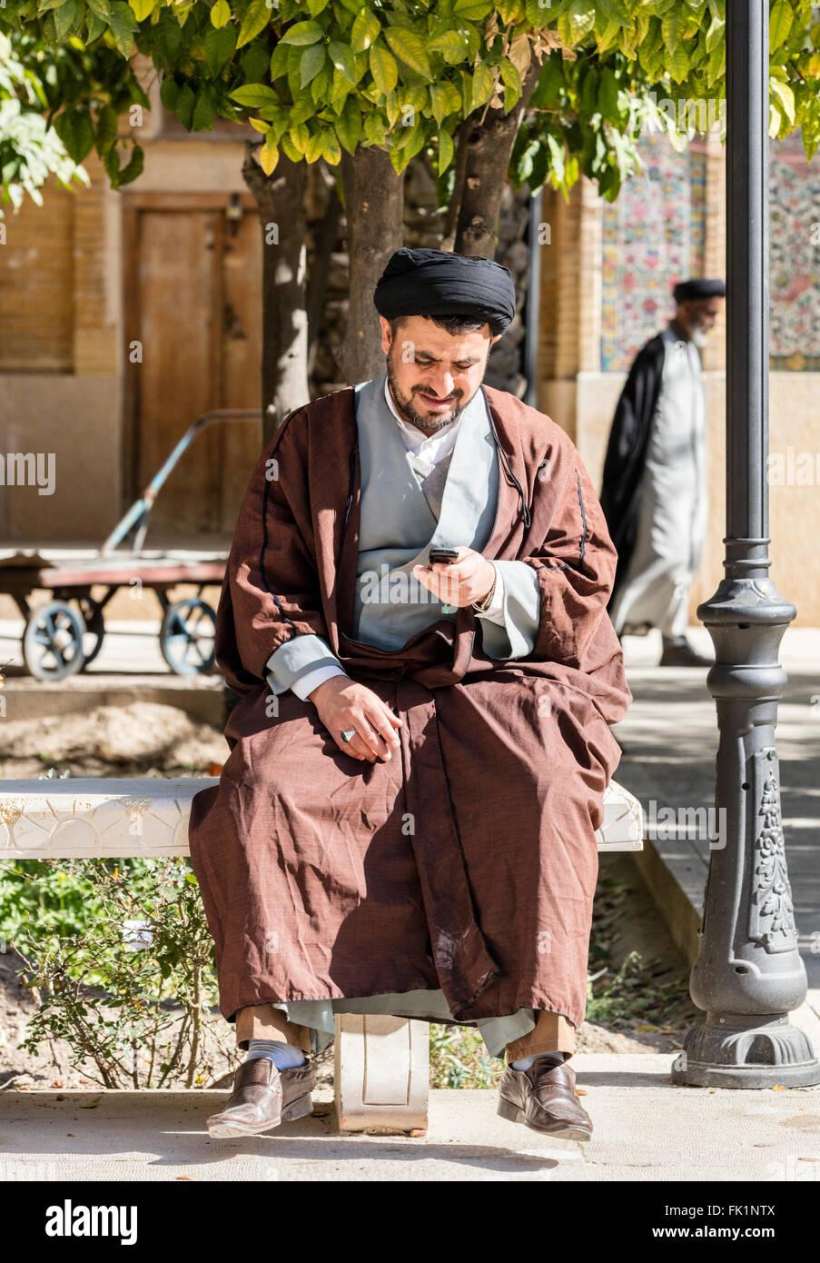 Mullah controlla il telefono cellulare mentre è seduto su una panchina presso il Khan Madrassa, Shiraz, Iran Immagini Stock