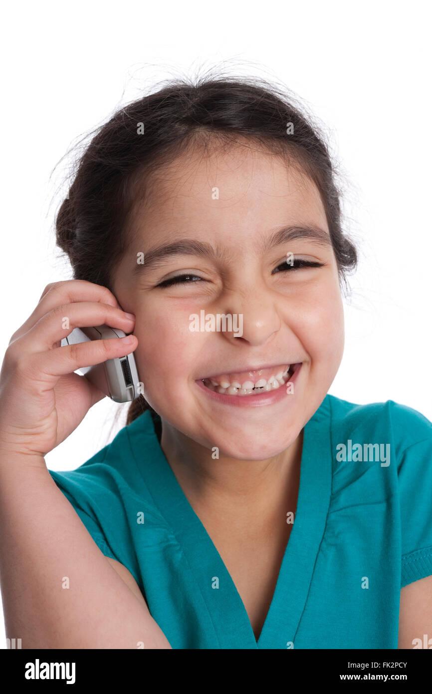 Bambina è è in ascolto per il suo telefono cellulare su sfondo bianco Immagini Stock