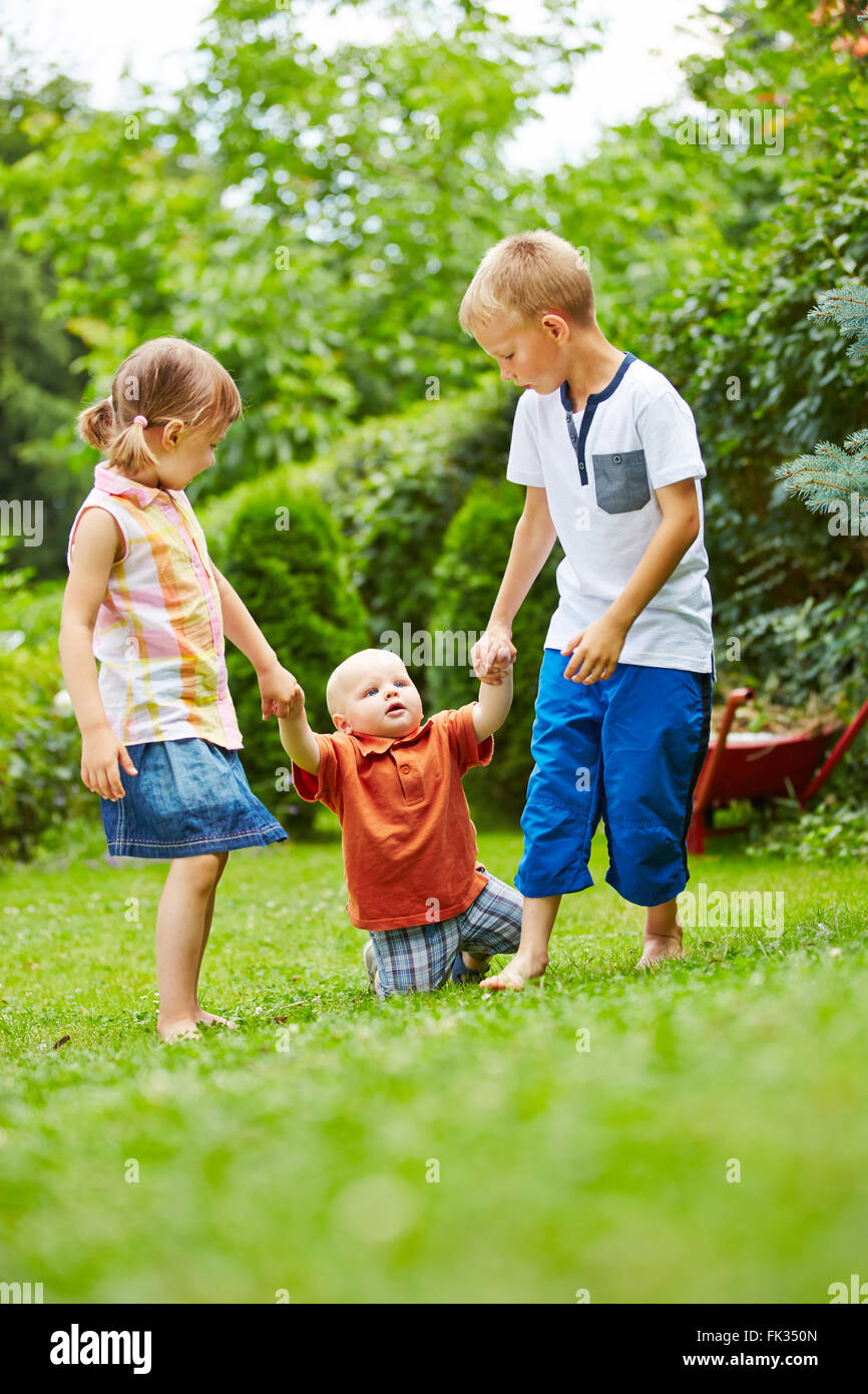 Due bambini disponibile ad aiutare il bambino ad imparare a camminare in un giardino in estate Foto Stock