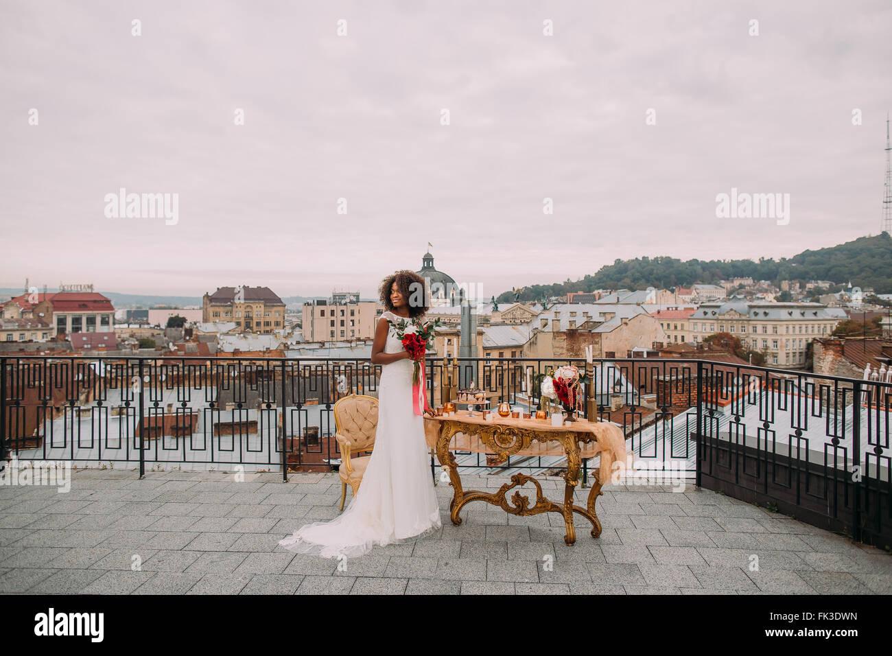 Bella sposa africana con bouquet di nozze in mani in piedi sulla terrazza Foto Stock
